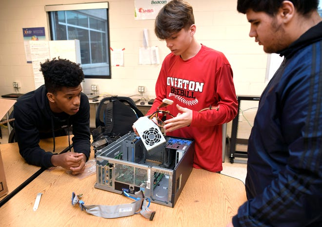 Overton High School students Robert Corbin, Jube Whitaker and Ava Hirori put a computer back together during Computer Networking class on Dec. 13, 2018.