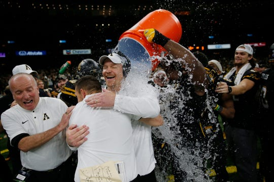 Appalachian State interim head coach Mark Ivey gets dunked by players in the closing seconds of their victory over Middle Tennessee in the New Orleans Bowl in New Orleans on Saturday. Appalachian State won 45-13. (AP Photo/Gerald Herbert)
