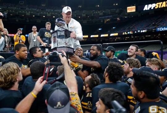 Appalachian State interim head coach Mark Ivey hands the bowl trophy to his team after the New Orleans Bowl against Middle Tennessee in New Orleans on Saturday. Appalachian State won 45-13. (AP Photo/Gerald Herbert)