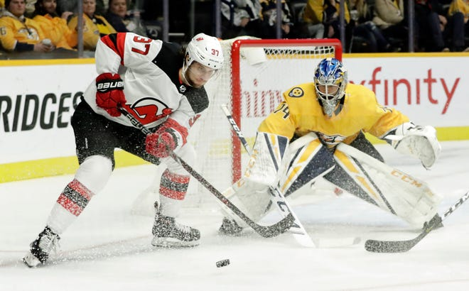 New Jersey Devils center Pavel Zacha (37), of the Czech Republic, reaches for the puck in front of Nashville Predators goaltender Juuse Saros (74), of Finland, in the first period of an NHL hockey game Saturday, Dec. 15, 2018, in Nashville, Tenn.