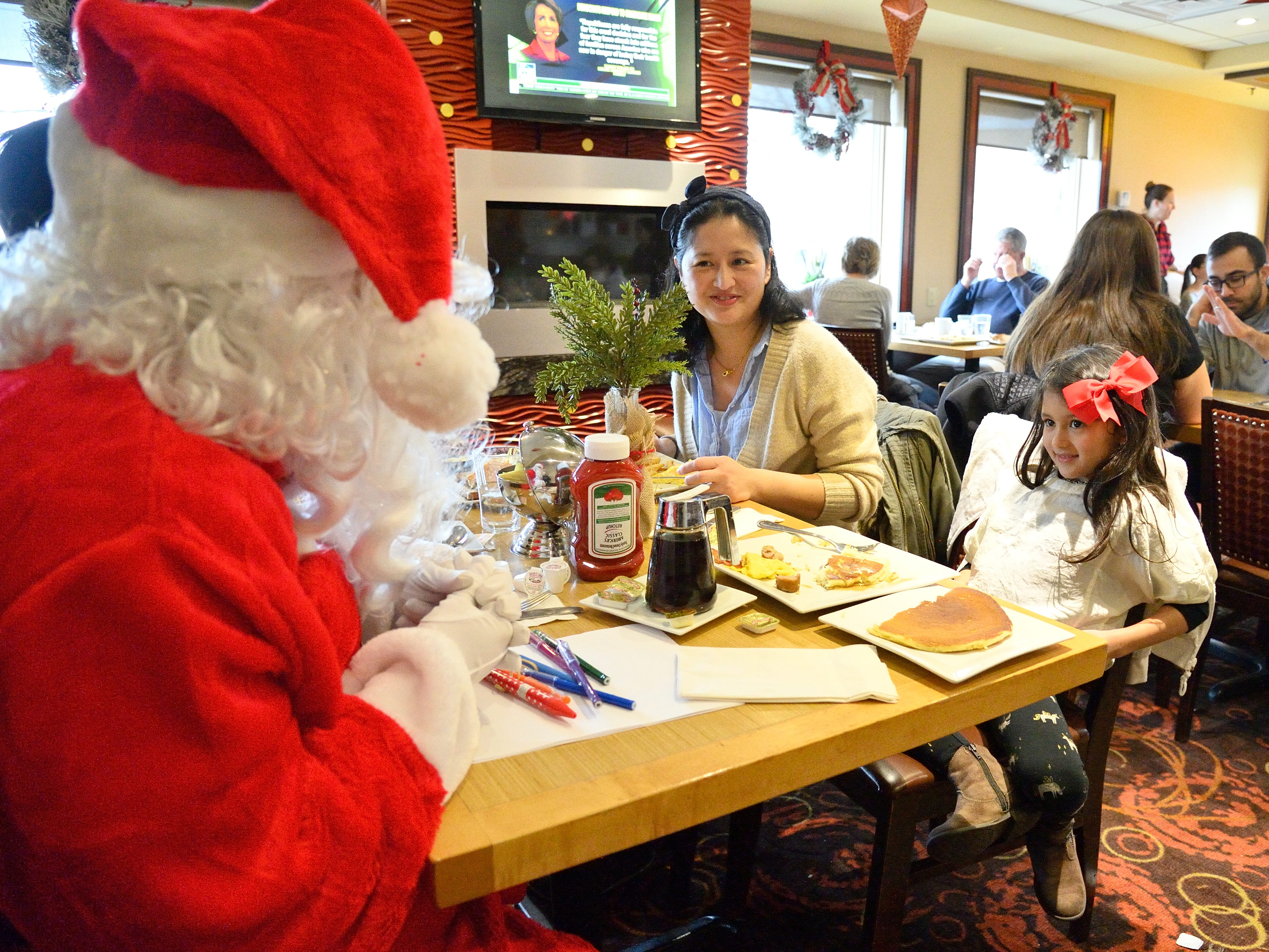 Santa greets Issara Hangsapruk and her mom Sonali at the Candlewyck Diner in East Rutherford on Saturday, Dec. 15, 2018