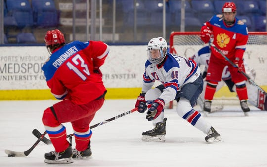 Team Russia's dangerous power play goes to work, as Vasili Ponomaryov (13) looks to send the puck past Team USA defenseman Jake Sanderson (48).