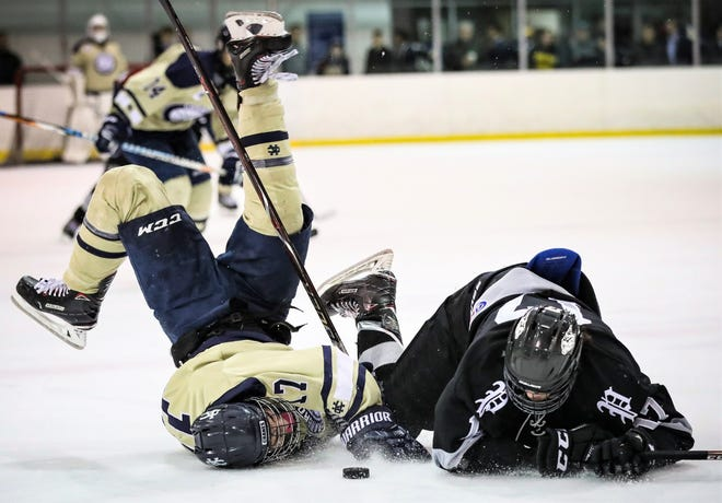 Cranbrook's Alex Ceritano (left) hits the ice hard after flipping over Plymouth's Nathan Stoneburg in the MIHL-KLAA Challenge Showcase at Edgar Arena.