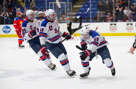 Ty Smilanic (59), celebrates with teammates Dylan Peterson (39) and Jake Sanderson (48) after scoring a power-play goal for Team USA.