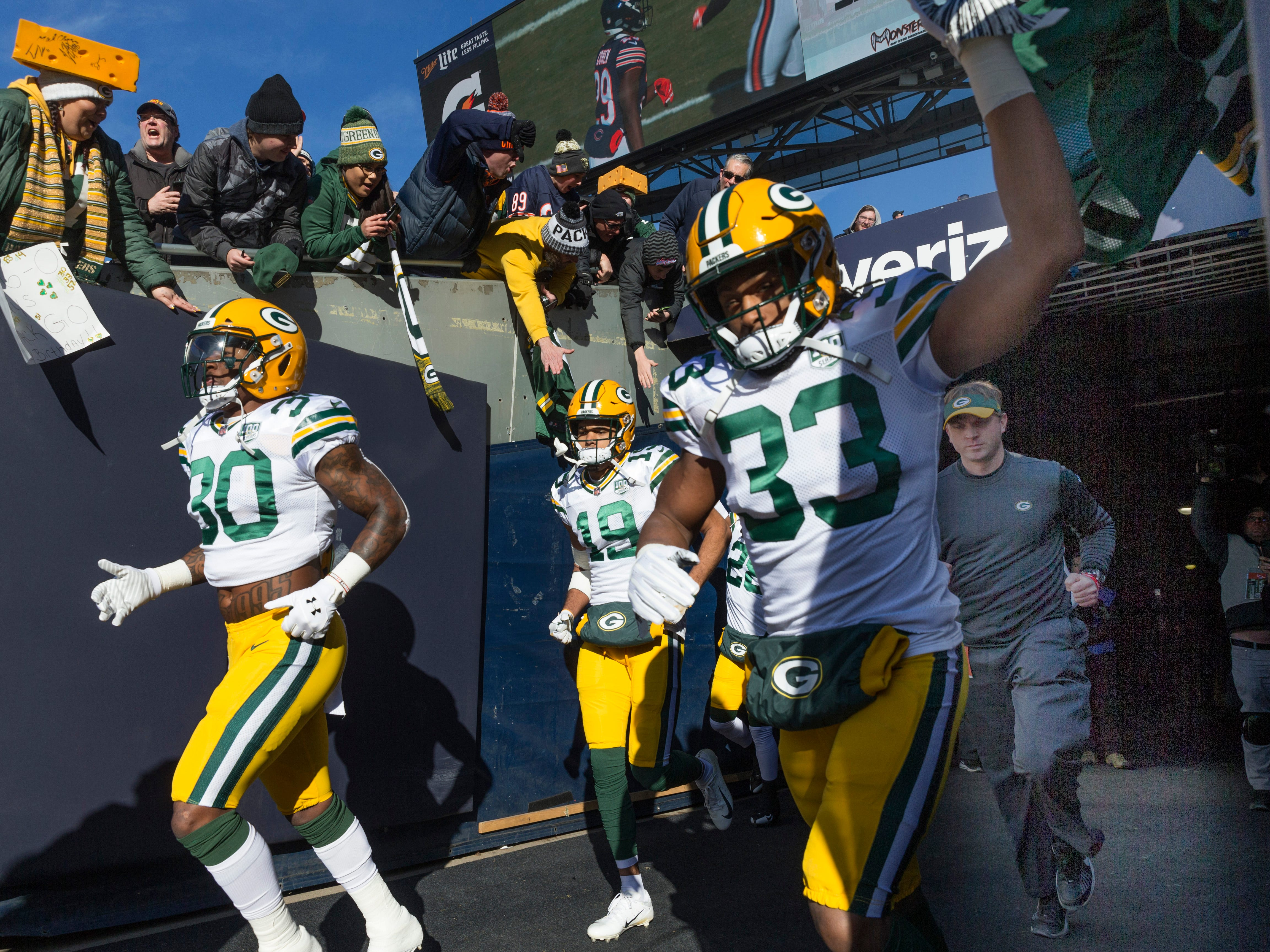 Green Bay Packers running back Jamaal Williams (30) and running back Aaron Jones (33) greet fans while taking to the field for warm ups  before their game against the Chicago Bears Sunday, December 25, 2018 at Soldier Field in Chicago, Ill.
