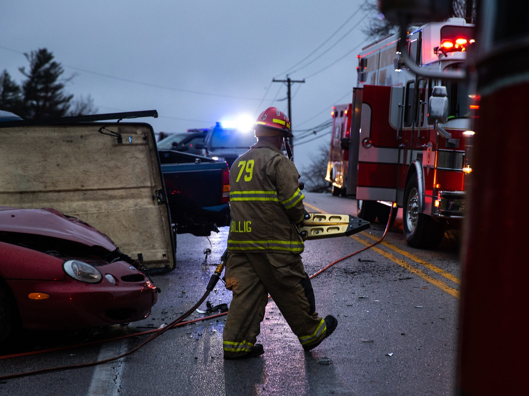 Firefighter Howard Billig carries away hydraulic rescue tools after using them to pop a car door open to gain better access to the flames at the scene of a three-vehicle crash with a fully involved car fire on the 2200 block of Broadway in Penn Township on Dec. 16. The fire resulted in three injuries, and two women were taken to the hospital following the crash, according to officials.