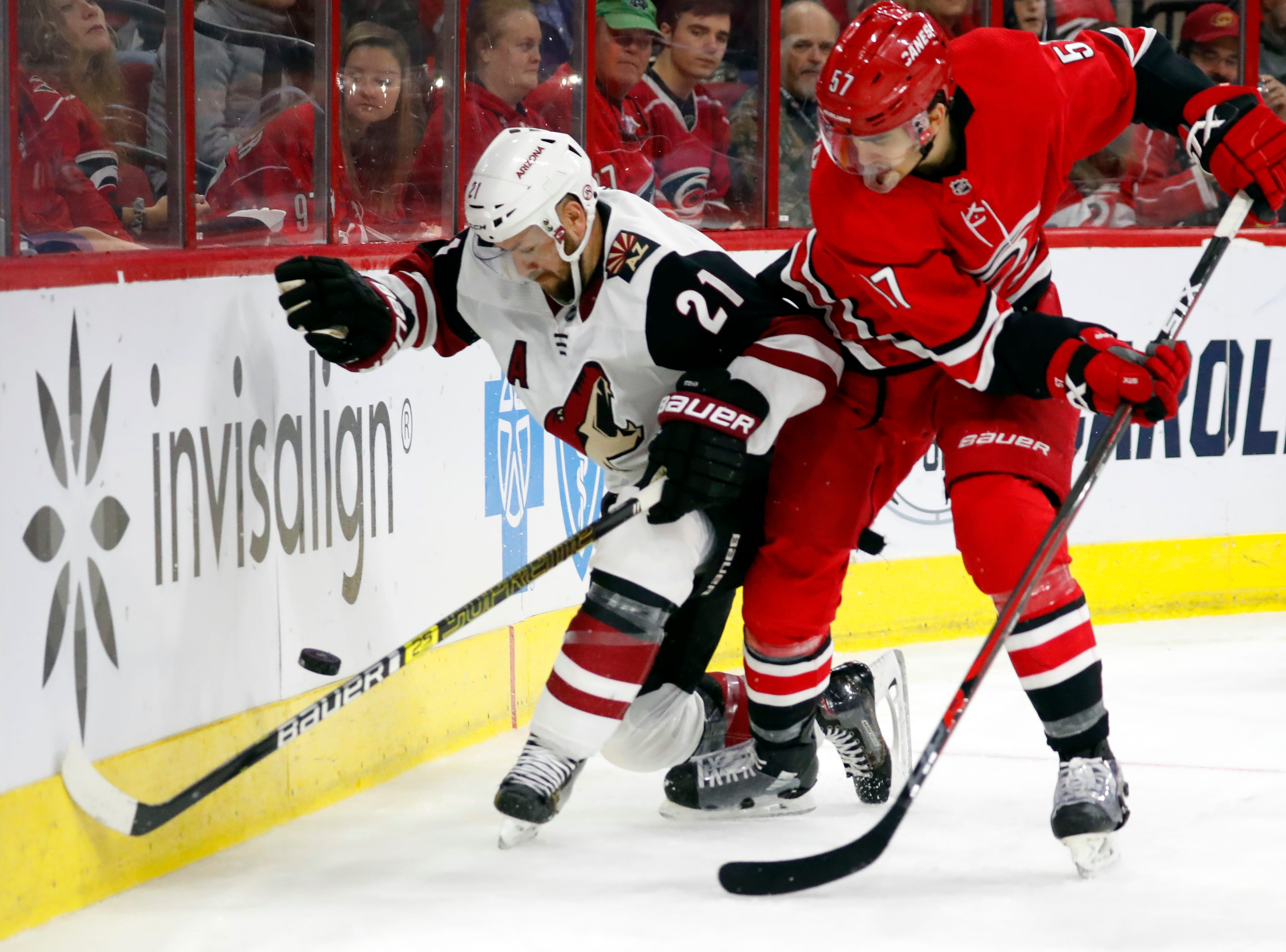 Carolina Hurricanes' Trevor van Riemsdyk (57) battles with Arizona Coyotes' Derek Stepan (21) during the second period of an NHL hockey game, Sunday, Dec. 16, 2018, in Raleigh, N.C.