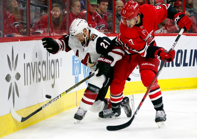 Carolina Hurricanes' Trevor van Riemsdyk (57) battles with Arizona Coyotes' Derek Stepan (21) during the second period of an NHL hockey game, Sunday, Dec. 16, 2018, in Raleigh, N.C.