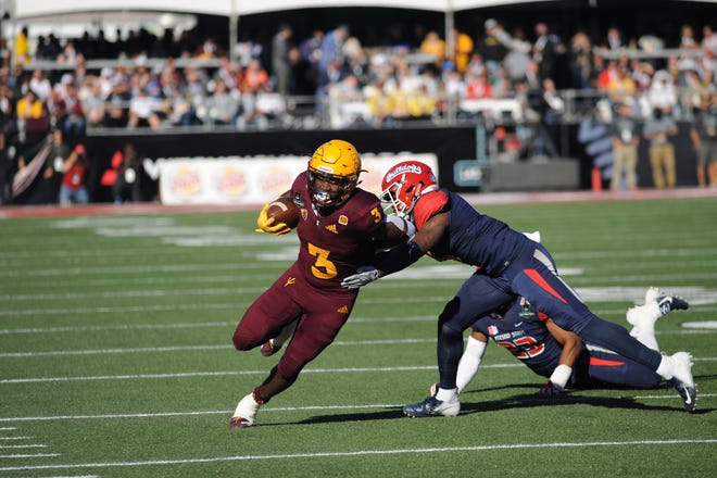 Arizona State running back Eno Benjamin (3) breaks a tackle attempt by Fresno State's Tank Kelly and Juju Hughes (23) during the first half of the Las Vegas Bowl Saturday, Dec. 15.