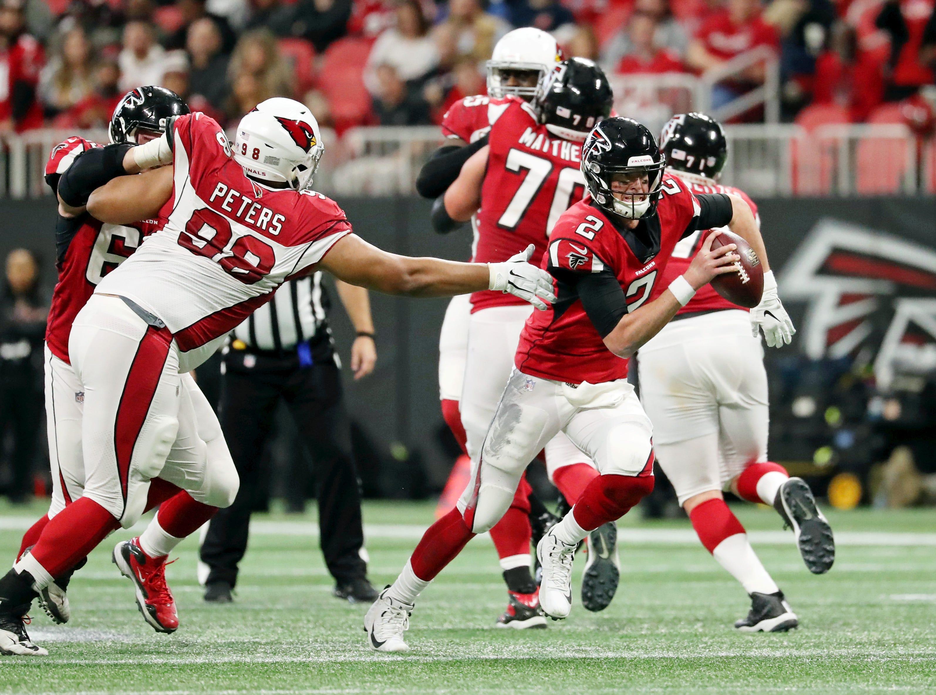 Dec 16, 2018; Atlanta, GA, USA; Atlanta Falcons quarterback Matt Ryan (2) runs past Arizona Cardinals defensive tackle Corey Peters (98) in the second quarter at Mercedes-Benz Stadium.