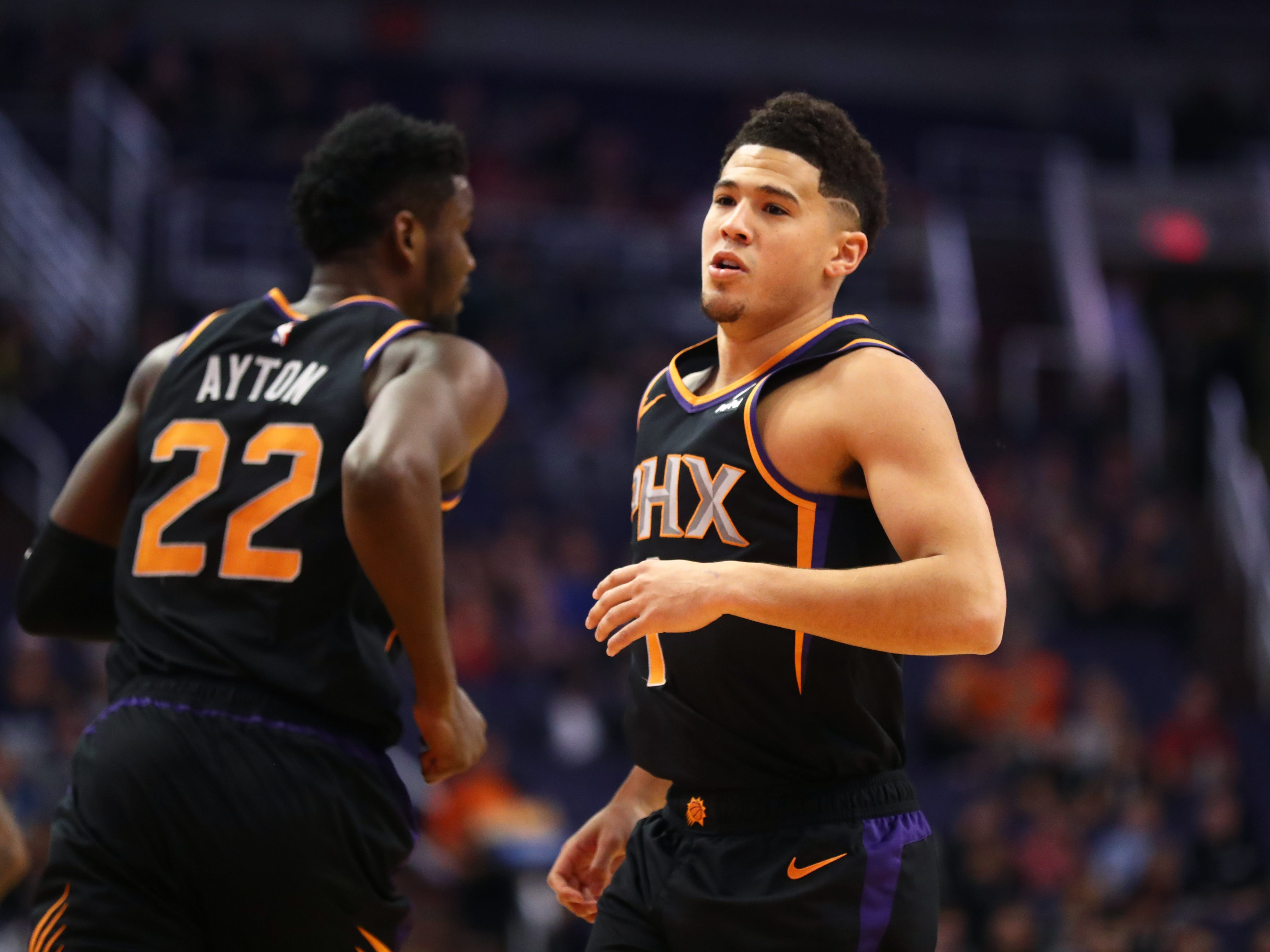 Dec 15, 2018; Phoenix, AZ, USA; Phoenix Suns guard Devin Booker (right) and center Deandre Ayton against the Minnesota Timberwolves in the first half at Talking Stick Resort Arena. Mandatory Credit: Mark J. Rebilas-USA TODAY Sports
