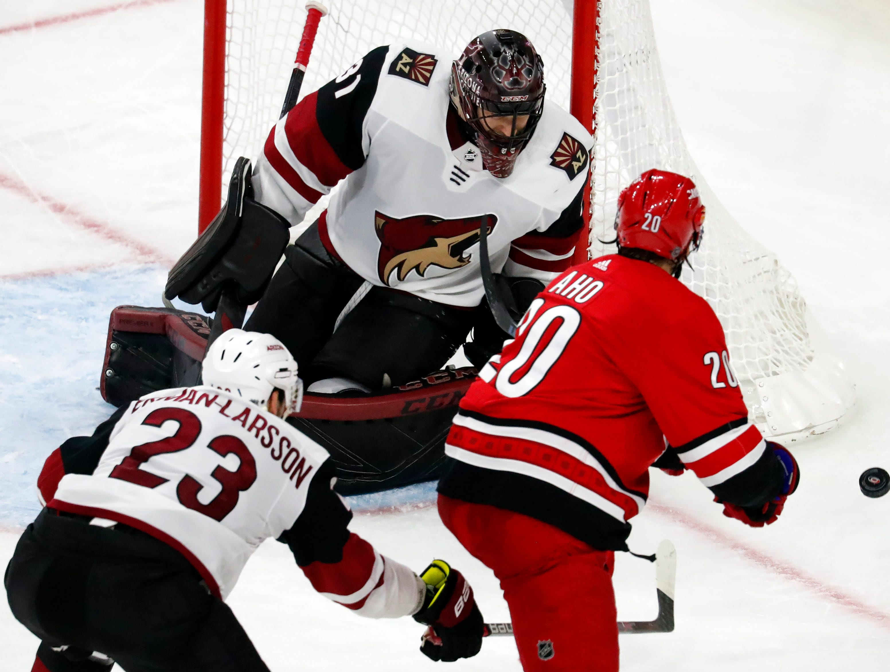 Arizona Coyotes goaltender Adin Hill (31) turns away a shot by Carolina Hurricanes' Sebastian Aho (20) with teammate Oliver Ekman-Larsson (23) nearby during the third period of an NHL hockey game, Sunday, Dec. 16, 2018, in Raleigh, N.C.
