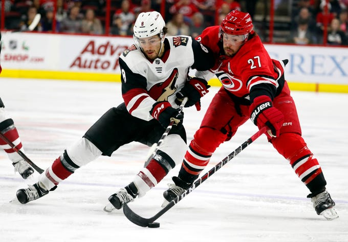 Arizona Coyotes' Nick Schmaltz (8) has the puck taken away by Carolina Hurricanes' Justin Faulk (27) during the second period of an NHL hockey game, Sunday, Dec. 16, 2018, in Raleigh, N.C.
