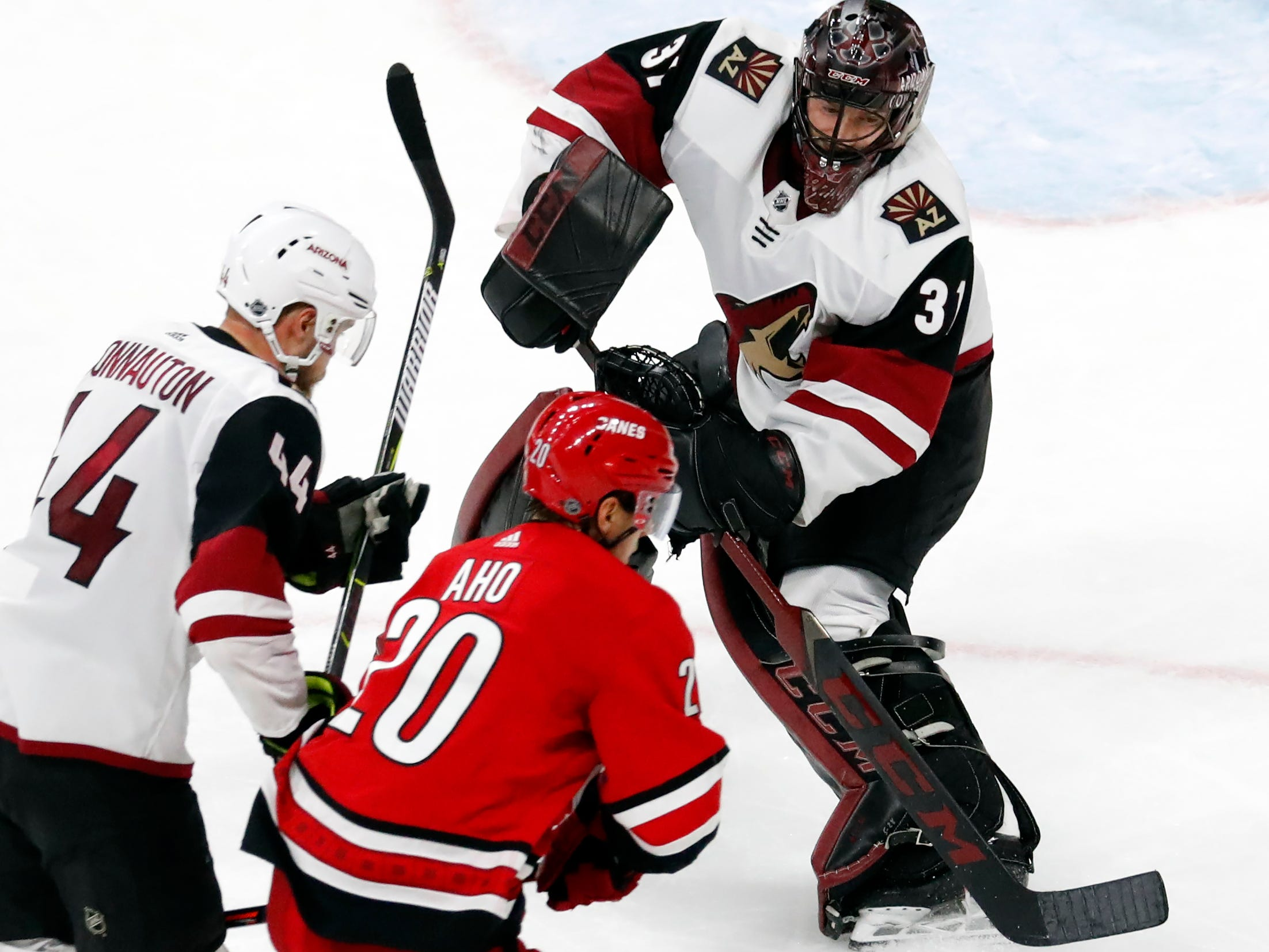 Arizona Coyotes goaltender Adin Hill (31) clears the puck in front of a charging Carolina Hurricanes' Sebastian Aho (20) and Coyotes Kevin Connauton (44) during the third period of an NHL hockey game, Sunday, Dec. 16, 2018, in Raleigh, N.C.
