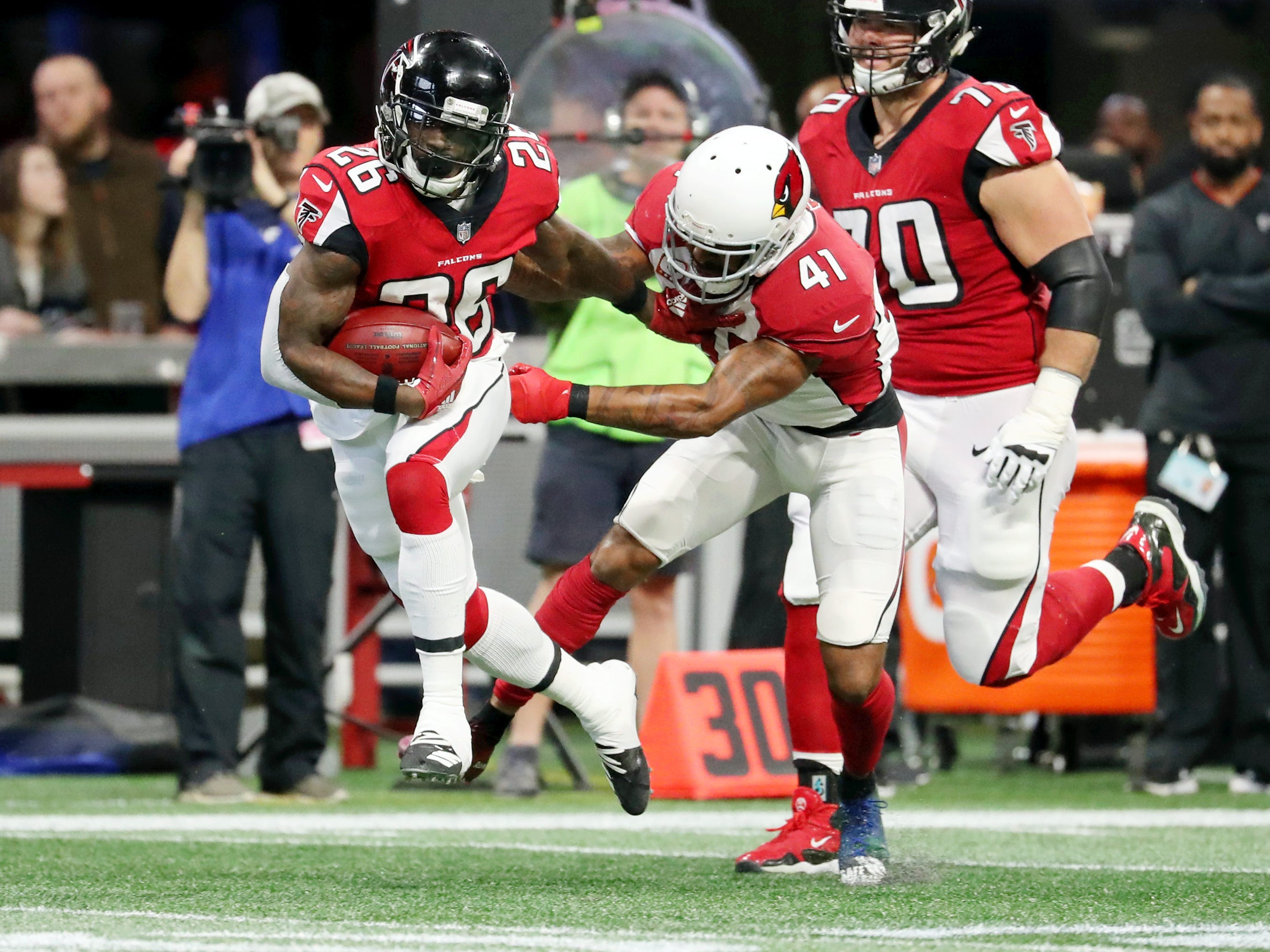Dec 16, 2018; Atlanta, GA, USA; Atlanta Falcons running back Tevin Coleman (26) runs against Arizona Cardinals free safety Antoine Bethea (41) on a long run in the first quarter at Mercedes-Benz Stadium.