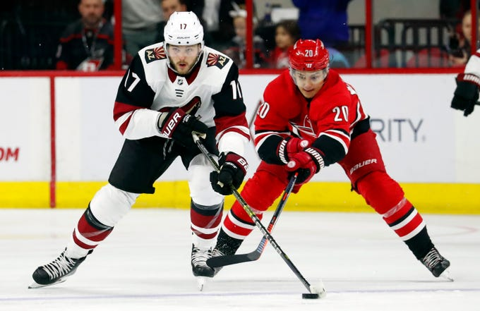 Arizona Coyotes' Alex Galchenyuk (17) keeps the puck away from Carolina Hurricanes' Sebastian Aho (20) during the first period of an NHL hockey game, Sunday, Dec. 16, 2018, in Raleigh, N.C.