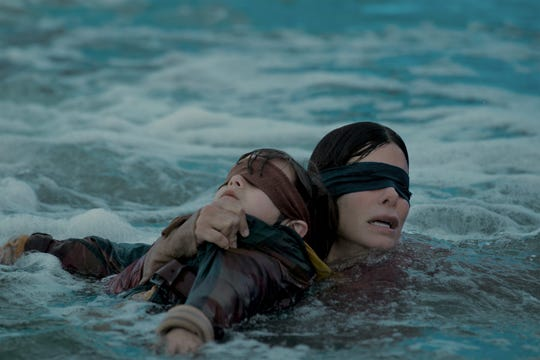 "In ""Bird Box,"" Malorie (Sandra Bullock) attempts to keep a youngster (Julian Edwards) safe."