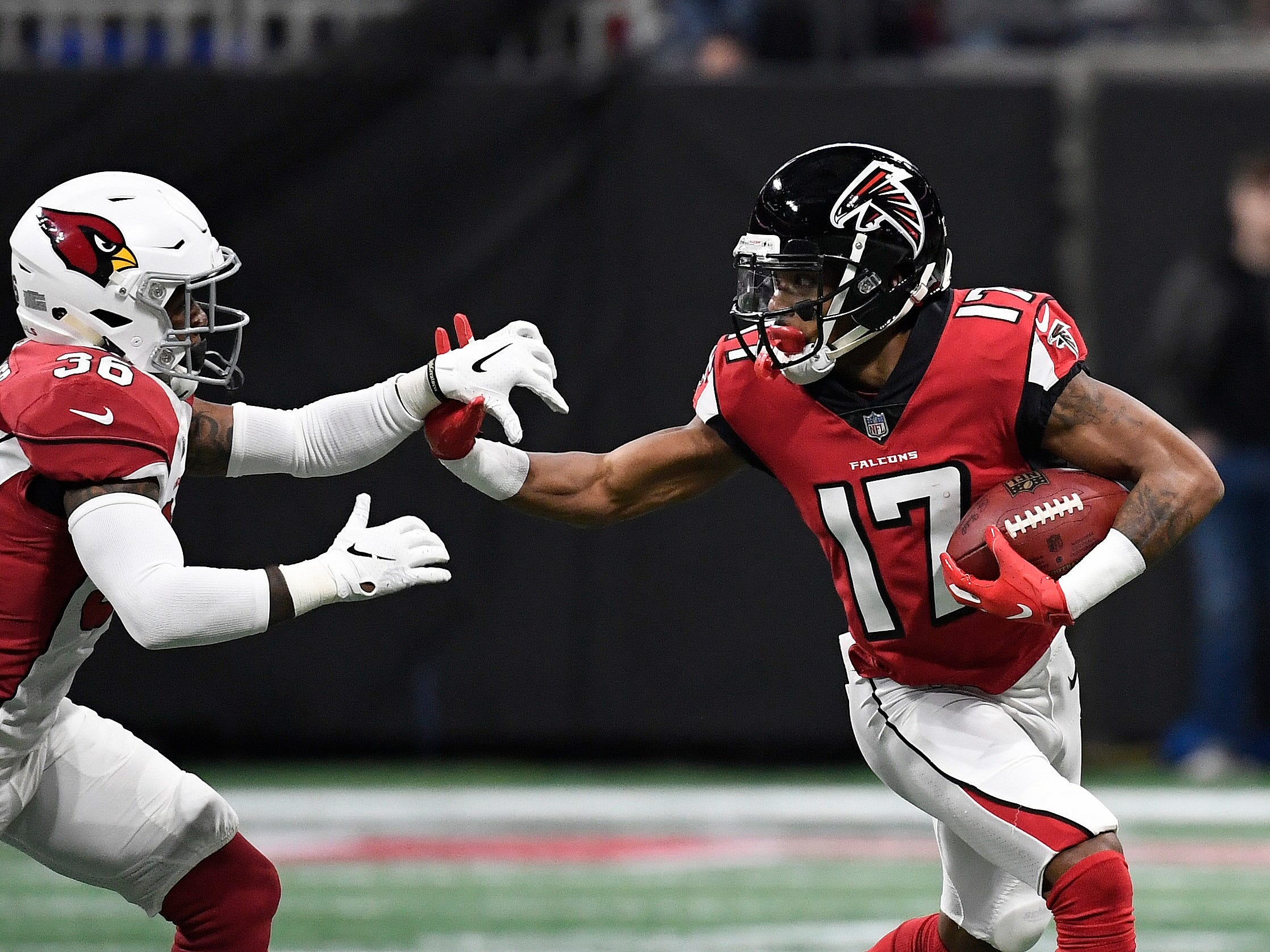Atlanta Falcons wide receiver Marvin Hall (17) fends off Arizona Cardinals strong safety Budda Baker (36) after a catch during the first half of an NFL football game, Sunday, Dec. 16, 2018, in Atlanta.
