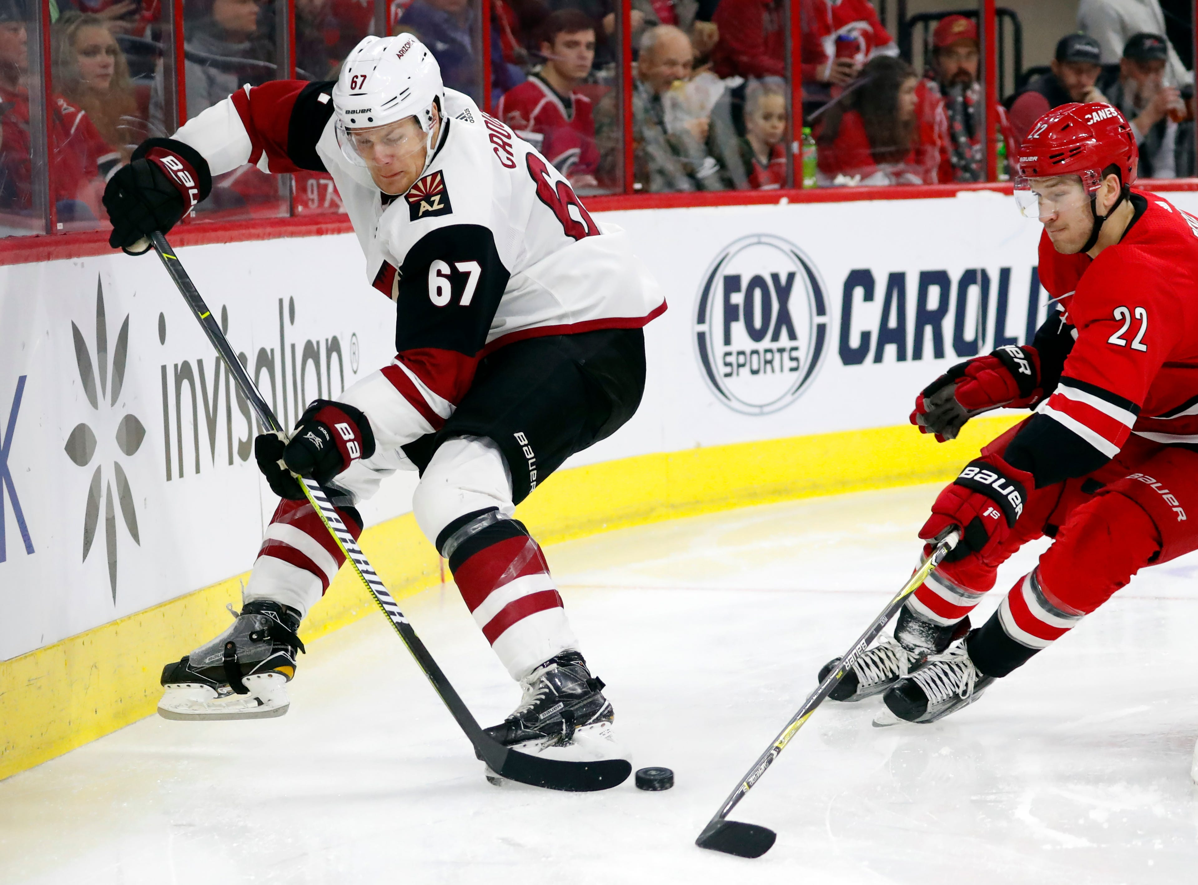 Arizona Coyotes' Lawson Crouse (67) battles behind the net with Carolina Hurricanes' Brett Pesce (22) during the second period of an NHL hockey game, Sunday, Dec. 16, 2018, in Raleigh, N.C.