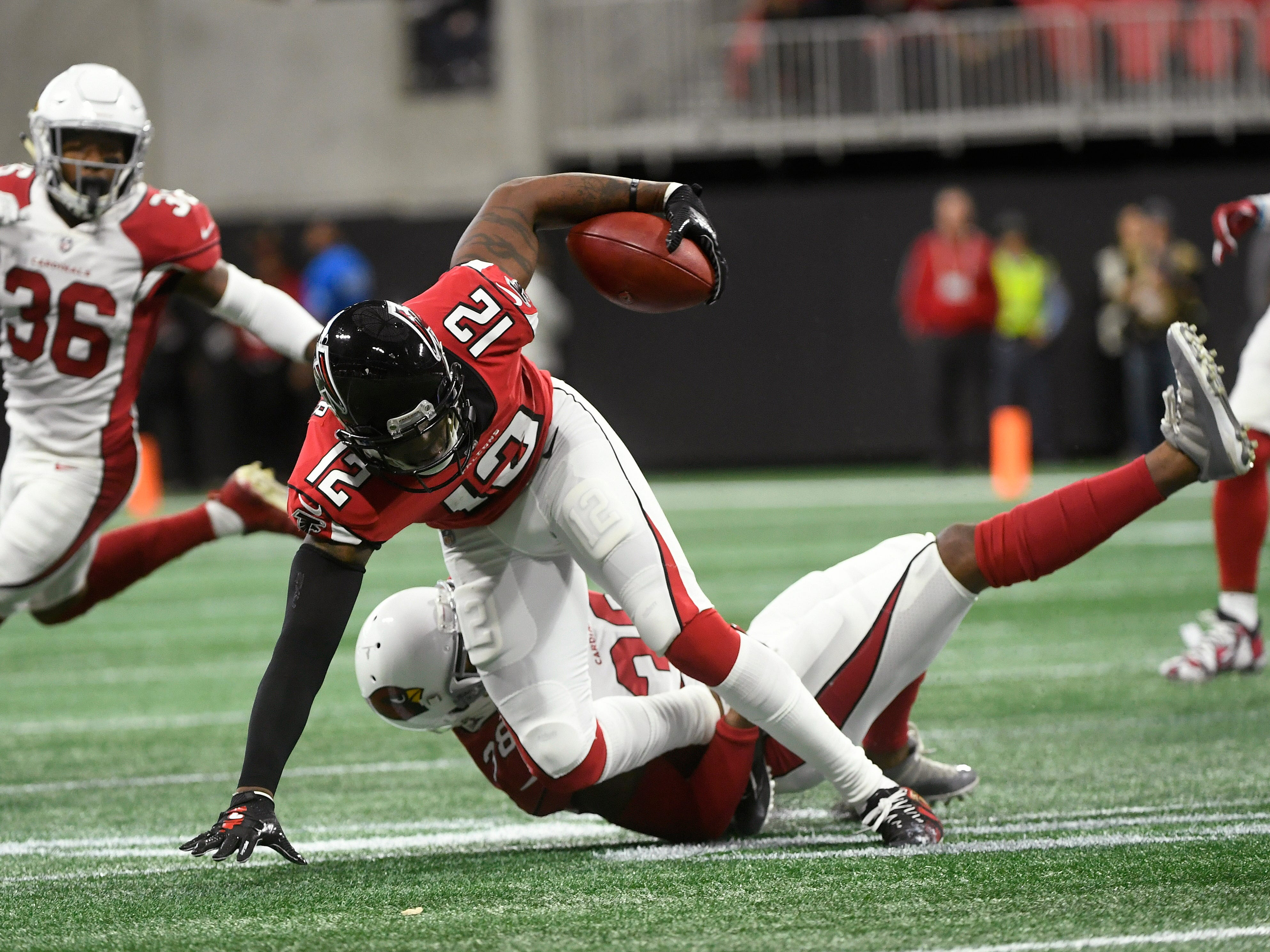 Arizona Cardinals defensive back David Amerson (38) tackles Atlanta Falcons cornerback Desmond Trufant (21) during the first half of an NFL football game, Sunday, Dec. 16, 2018, in Atlanta. (AP Photo/John Amis)