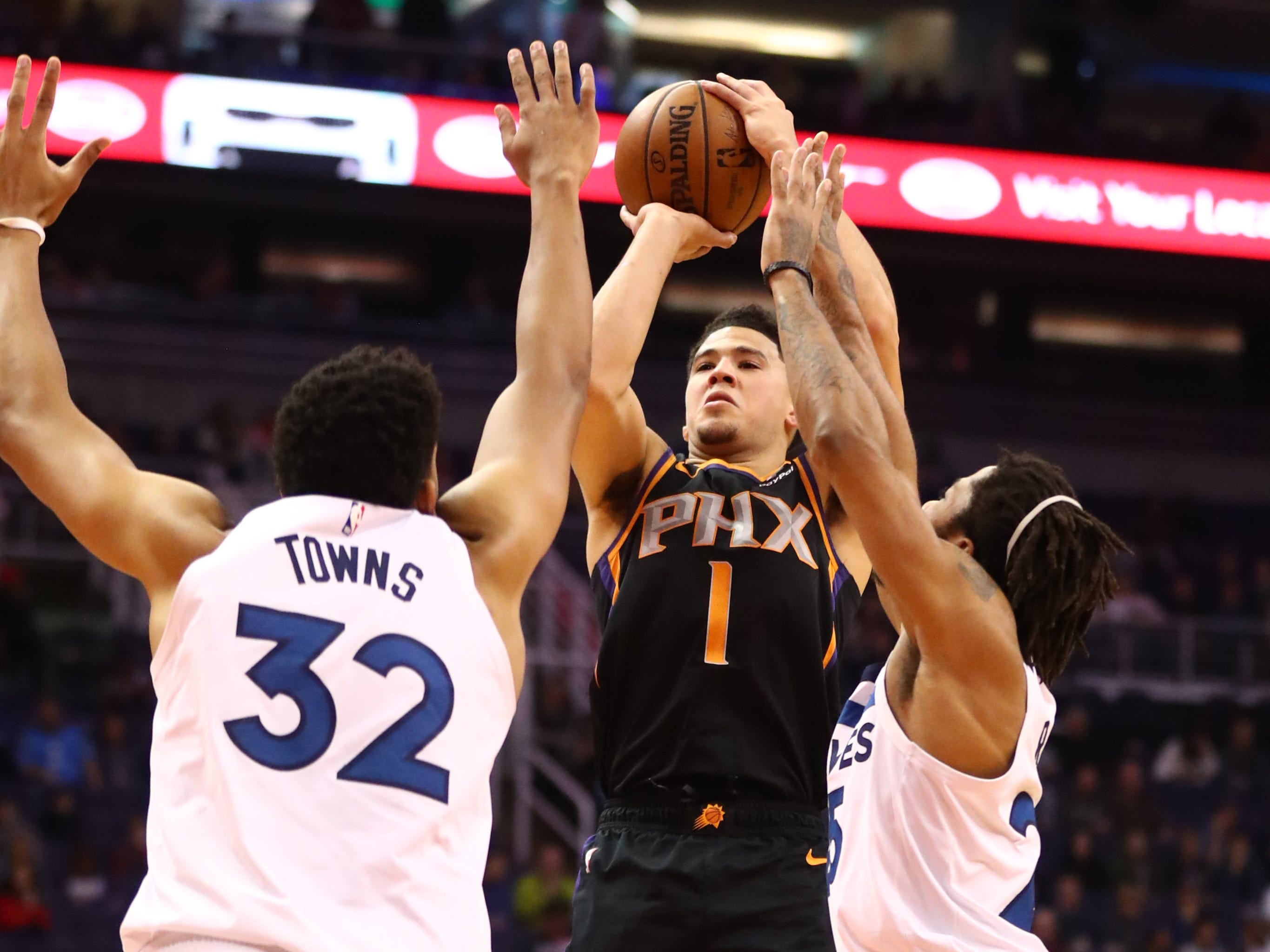 Dec 15, 2018; Phoenix, AZ, USA; Phoenix Suns guard Devin Booker (1) shoots the ball against Minnesota Timberwolves center Karl-Anthony Towns at Talking Stick Resort Arena. Mandatory Credit: Mark J. Rebilas-USA TODAY Sports