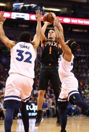 Dec 15, 2018; Phoenix, AZ, USA; Phoenix Suns guard Devin Booker (1) shoots the ball against Minnesota Timberwolves center Karl-Anthony Towns at Talking Stick Resort Arena. Mandatory Credit: Mark J. Rebilas-USA TODAY Sports