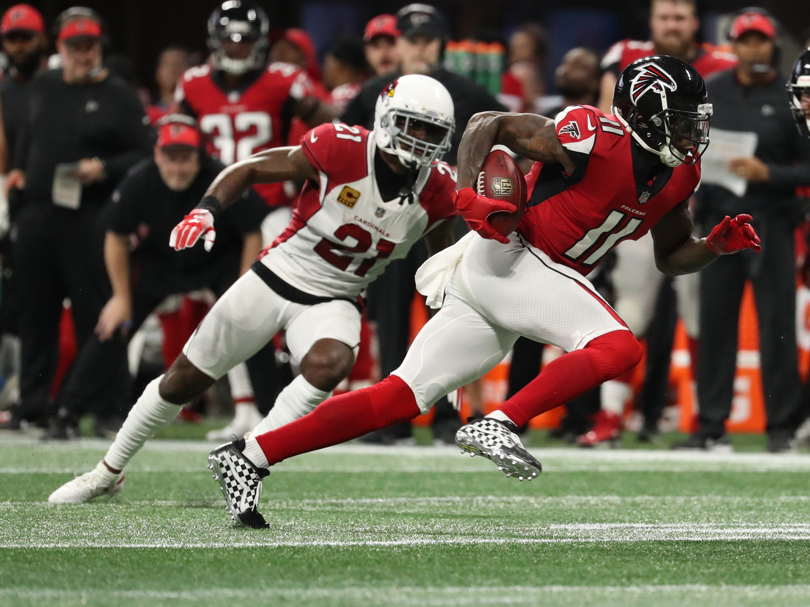 Dec 16, 2018; Atlanta, GA, USA; Atlanta Falcons wide receiver Julio Jones (11) runs after a catch against Arizona Cardinals cornerback Patrick Peterson (21) in the second quarter at Mercedes-Benz Stadium.
