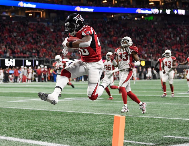Atlanta Falcons running back Tevin Coleman (26) leaps into the end zone as he scores on a pass from Matt Ryan during the second half of an NFL football game against the Arizona Cardinals, Sunday, Dec. 16, 2018, in Atlanta.