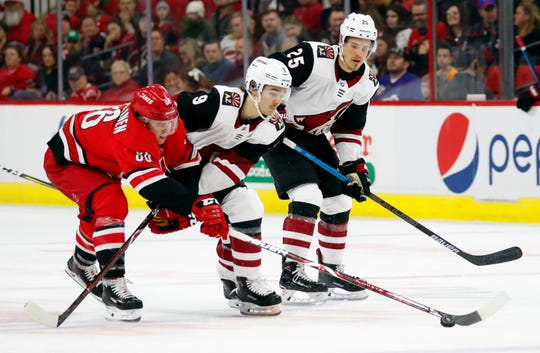 Carolina Hurricanes' Teuvo Teravainen (86) tips the puck away from Arizona Coyotes' Clayton Keller (9) with Coyotes' Nick Cousins (25) looking on during the first period of an NHL hockey game, Sunday, Dec. 16, 2018, in Raleigh, N.C.