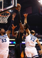 Dec 15, 2018; Phoenix, AZ, USA; Phoenix Suns center Deandre Ayton (center) drives to the basket against Minnesota Timberwolves center Karl-Anthony Towns (32) and forward Robert Covington (33) in the first half at Talking Stick Resort Arena. Mandatory Credit: Mark J. Rebilas-USA TODAY Sports