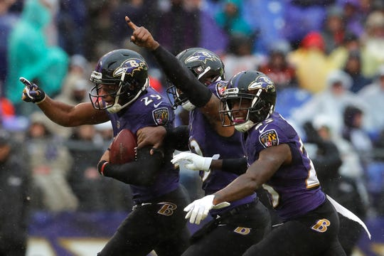 Baltimore Ravens cornerback Marlon Humphrey, left, celebrates with teammates after intercepting a pass attempt in the second half of an NFL football game against the Tampa Bay Buccaneers, Sunday, Dec. 16, 2018, in Baltimore. (AP Photo/Carolyn Kaster)