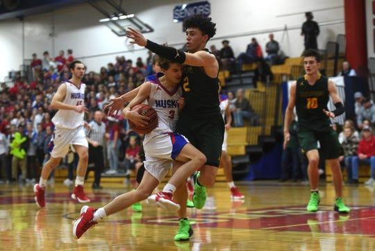 Reno's Nick Gonzalez runs into Bishop Manogue's Gabe Bansuelo during their basketball game in Reno on Dec. 14.
