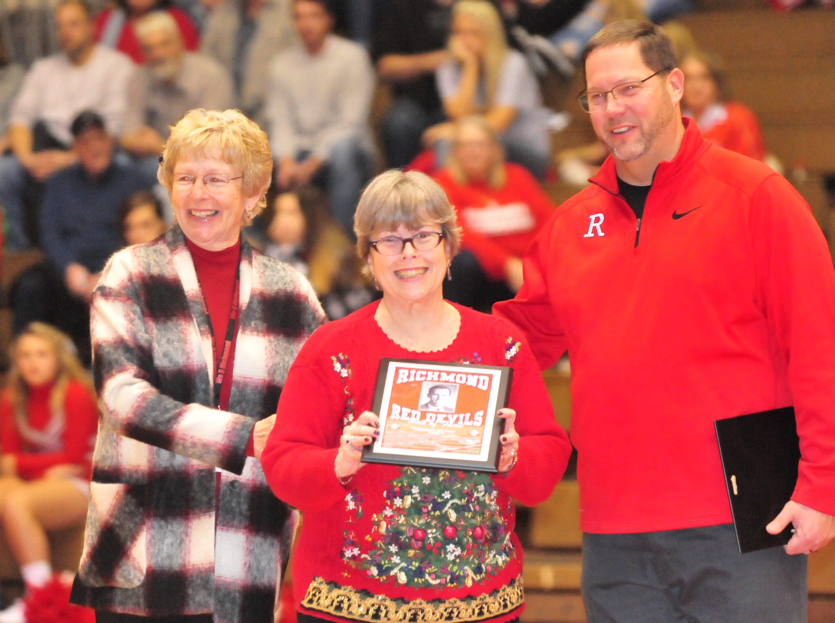 Family of Charlie Hilton, center, accepts Hilton's plaque as they were among the seven inducted into the inaugural RHS Coaches Hall of Fame during Saturday's 42-39 boys basketball loss to Connersville Dec. 15, 2018 at Tiernan Center.
