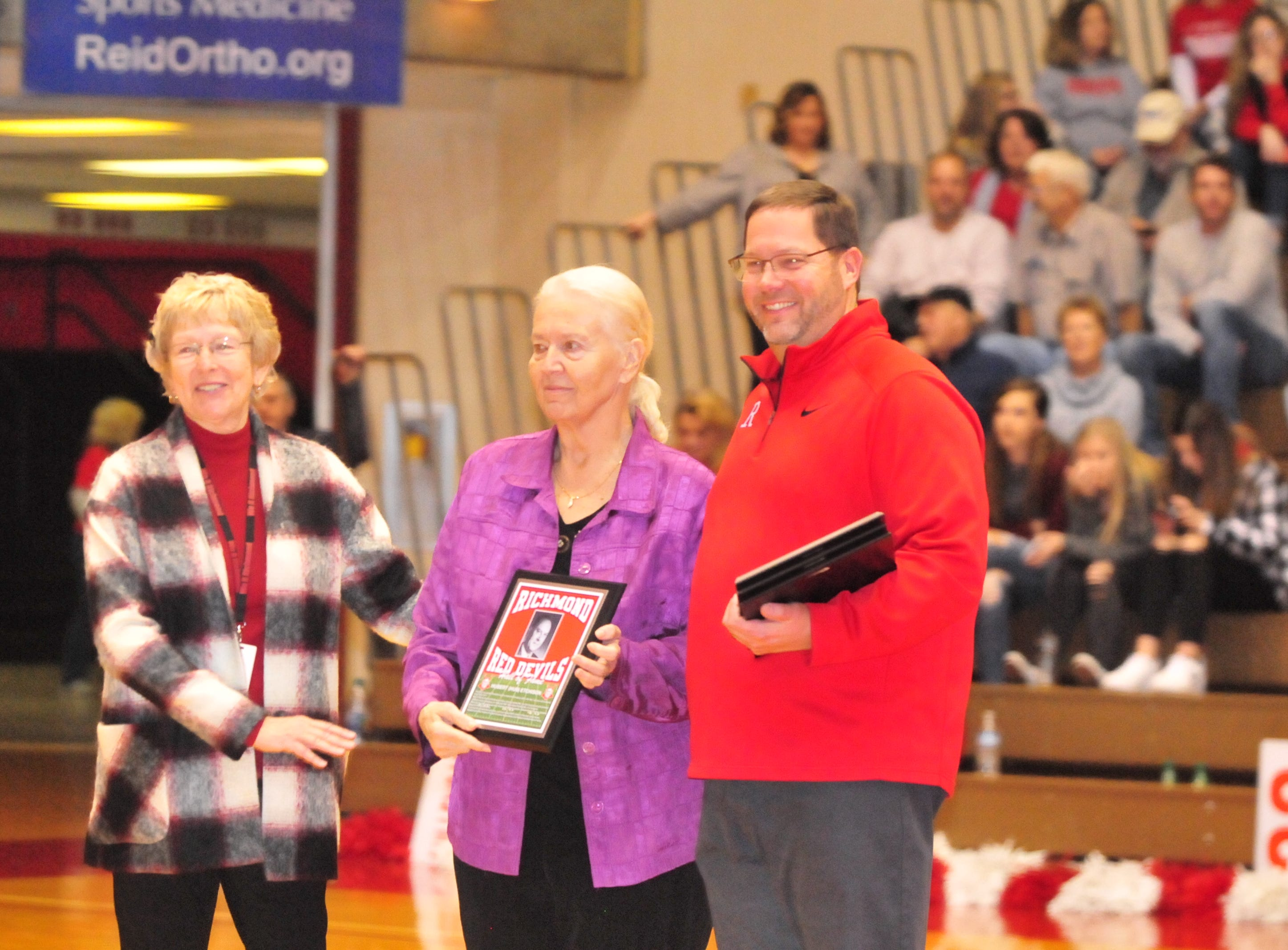 Family members of Hub Etchison accept his plaque as he was one of seven inducted into the inaugural RHS Coaches Hall of Fame during Saturday's 42-39 boys basketball loss to Connersville Dec. 15, 2018 at Tiernan Center.