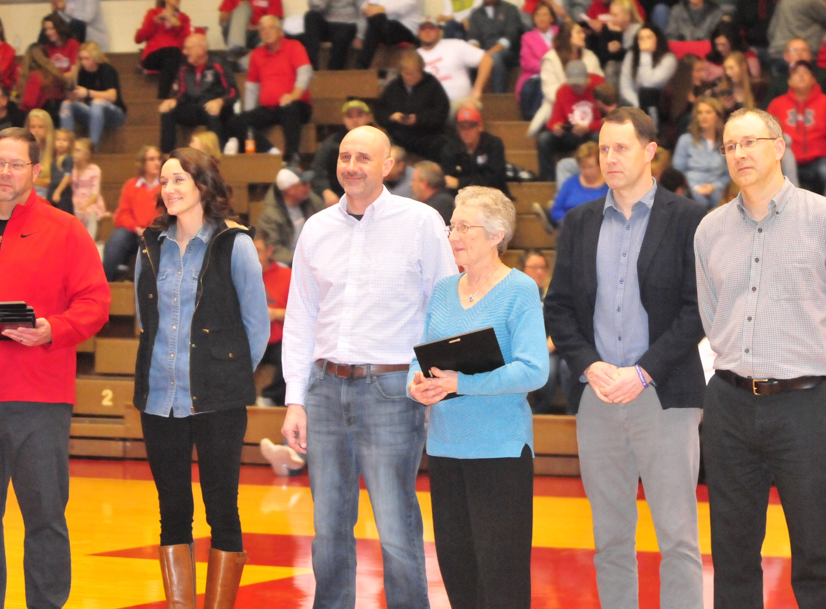 Family members of Dave Bowers accept his plaque as he was one of seven inducted into the inaugural RHS Coaches Hall of Fame during Saturday's 42-39 boys basketball loss to Connersville Dec. 15, 2018 at Tiernan Center.