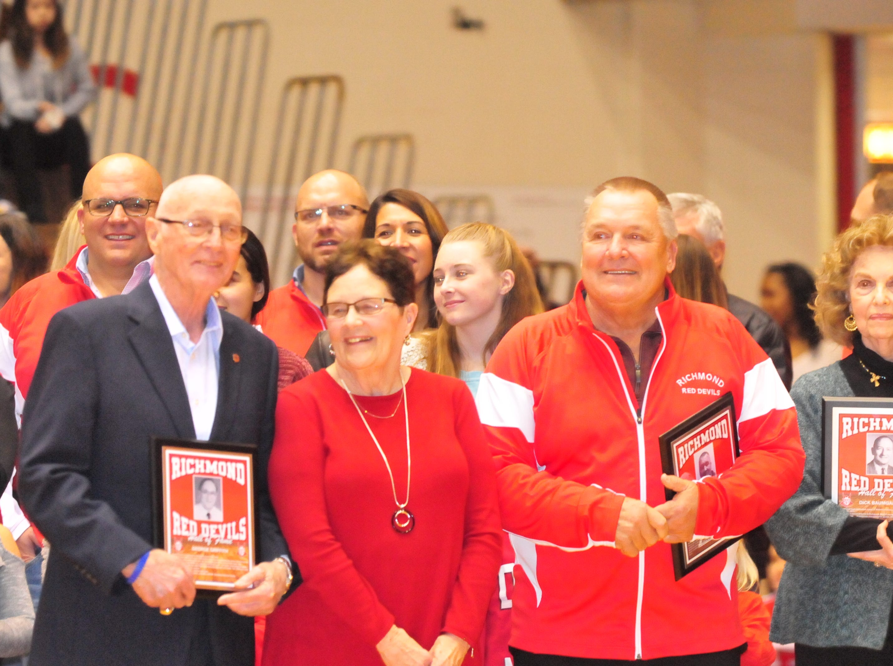 George Griffith, center left, his wife Ann, and John Cate talk after accepting their plaques as they were among the seven inducted into the inaugural RHS Coaches Hall of Fame during Saturday's 42-39 boys basketball loss to Connersville Dec. 15, 2018 at Tiernan Center.