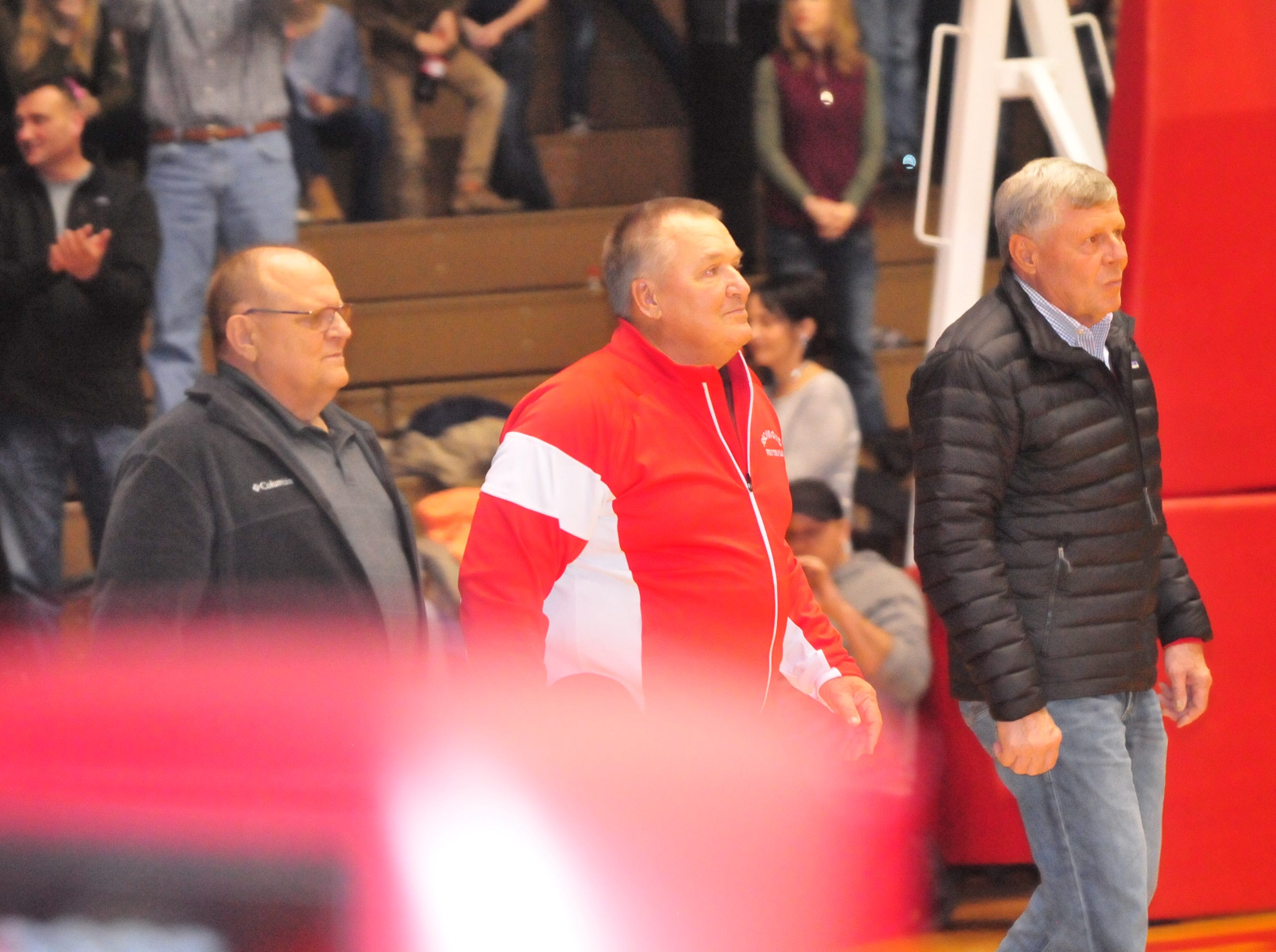 John Cate (center) accepts his plaque as he was one of seven inducted into the inaugural RHS Coaches Hall of Fame during Saturday's 42-39 boys basketball loss to Connersville Dec. 15, 2018 at Tiernan Center.