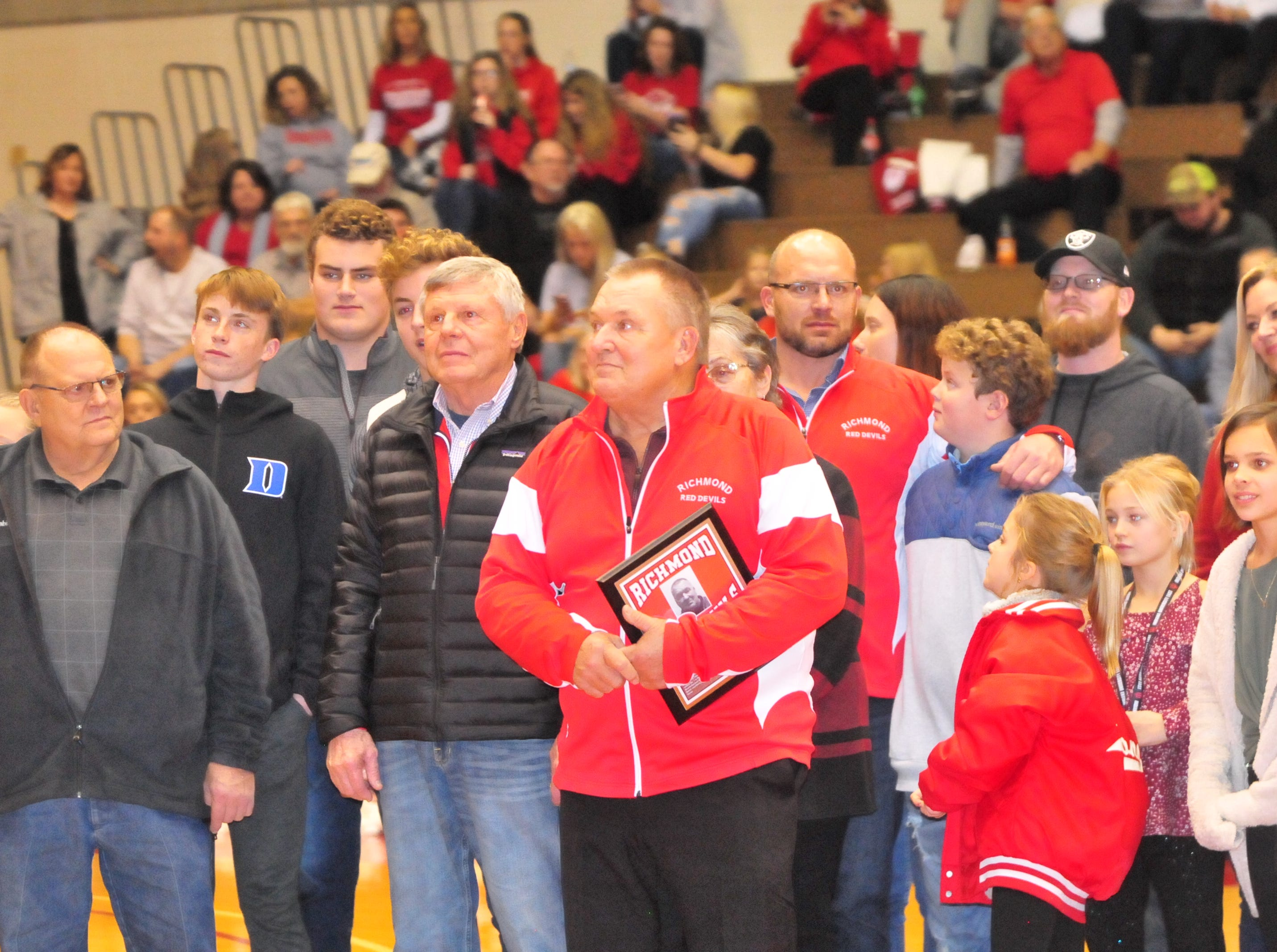 John Cate (center holding plaque) is joined by several family members after accepting his plaque as he was one of seven inducted into the inaugural RHS Coaches Hall of Fame during Saturday's 42-39 boys basketball loss to Connersville Dec. 15, 2018 at Tiernan Center.