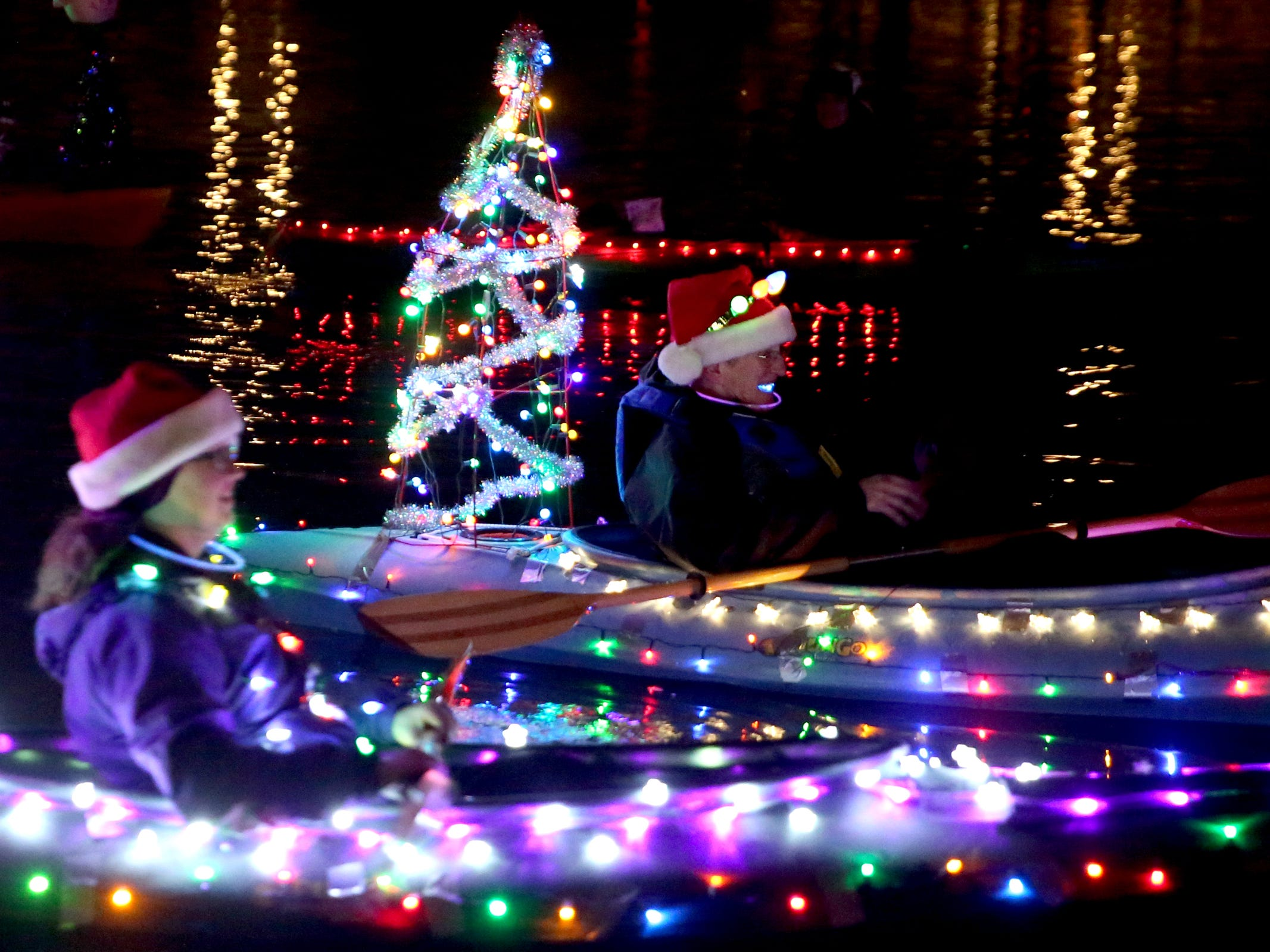 Women kayak during the 14th annual Winter Solstice Illuminata Regatta on the Willamette River at Riverfront Park in Salem on Saturday, Dec. 15, 2018.