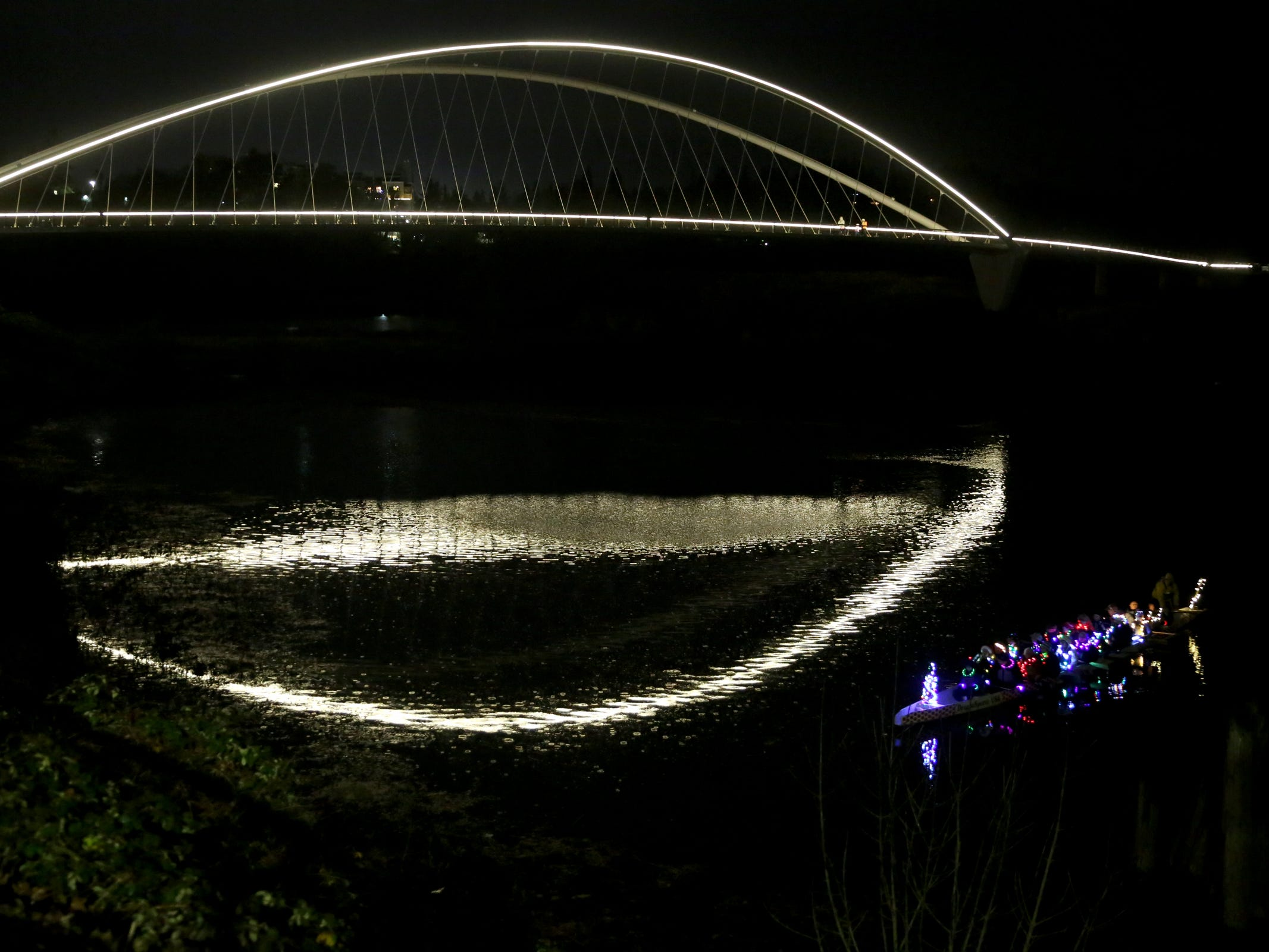 A dragon boat floats near the Peter Courtney Pedestrian Bridge during the 14th annual Winter Solstice Illuminata Regatta on the Willamette River at Riverfront Park in Salem on Saturday, Dec. 15, 2018.
