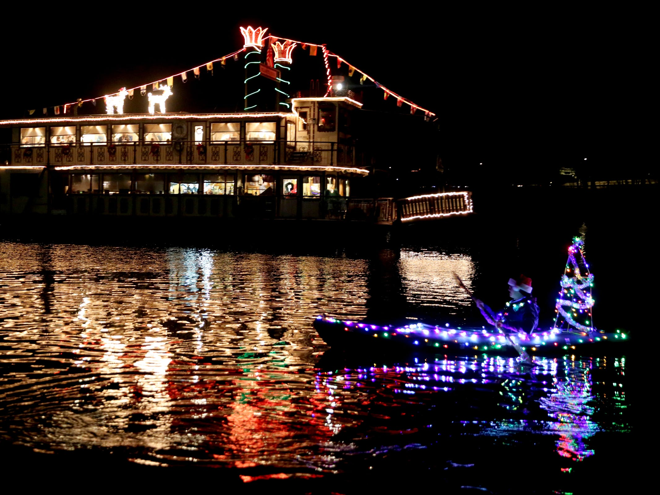 A woman kayaks near the Willamette Queen sternwheeler during the 14th annual Winter Solstice Illuminata Regatta on the Willamette River at Riverfront Park in Salem on Saturday, Dec. 15, 2018.