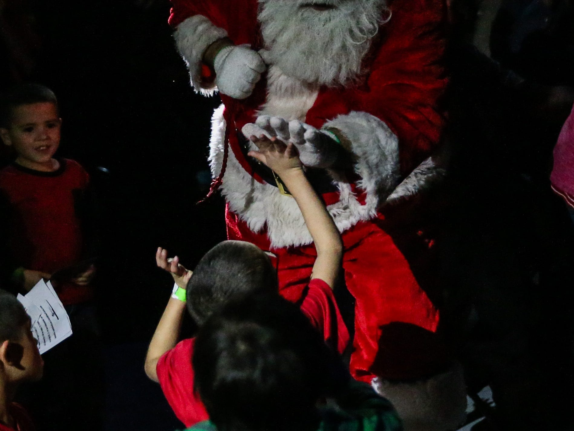 Santa greets a kid as he makes his way through the crowd at the In the Spirit of Christmas party Saturday, Dec. 15, 2018, at the Southside Recreation Center.