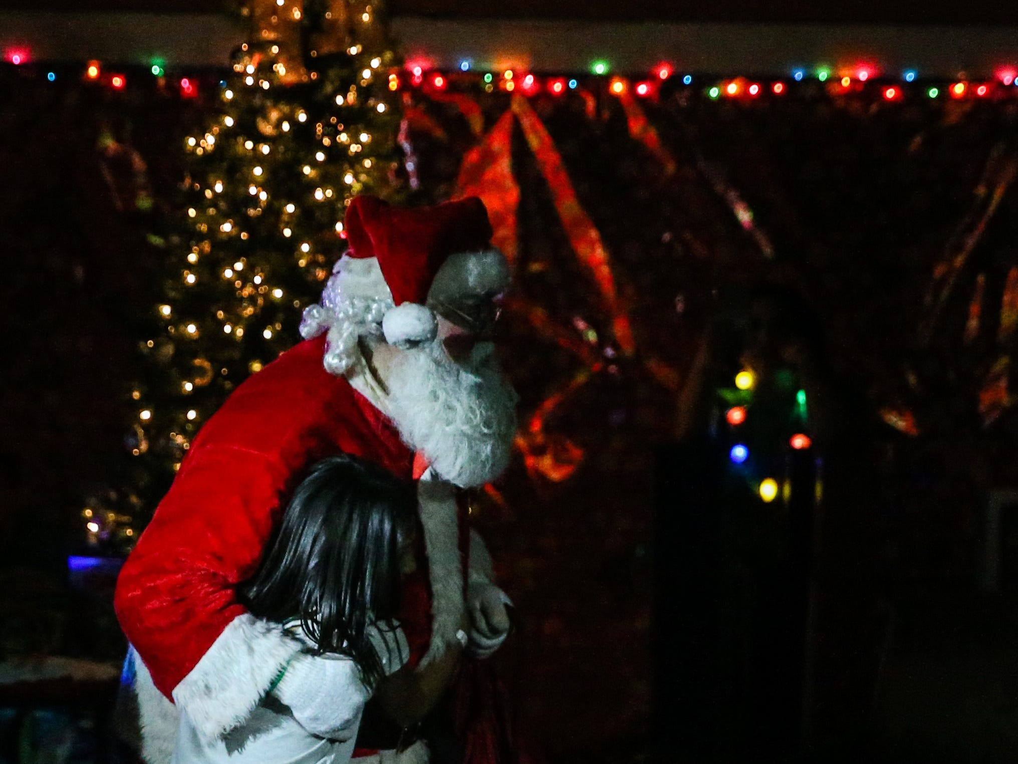 Santa is hugged by a girl as he makes his way through the crowd at the In the Spirit of Christmas party Saturday, Dec. 15, 2018, at the Southside Recreation Center.