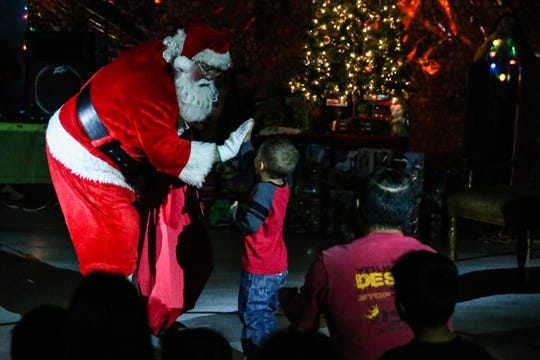 Santa high fives a kid as he makes his way through the crowd at the In the Spirit of Christmas party Saturday, Dec. 15, 2018, at the Southside Recreation Center.