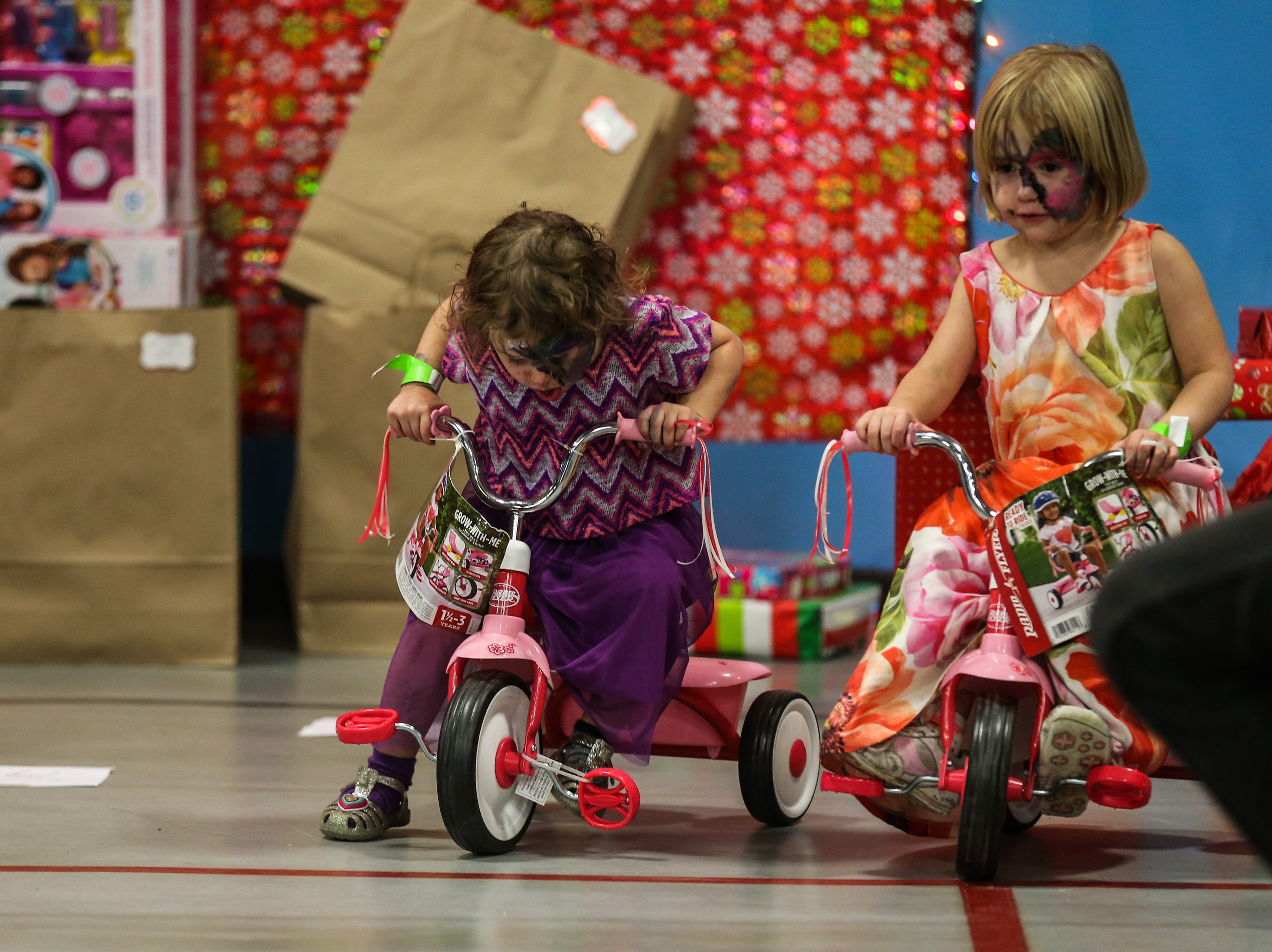Happie Blazek, 2, and Prairie Blazek, 4, try out tricycles from the gifts  during the In the Spirit of Christmas party Saturday, Dec. 15, 2018, at the Southside Recreation Center.