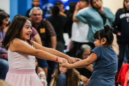 Jazmin Navarro, 8, and Noemi Gaitan, 9, dance during the In the Spirit of Christmas party Saturday, Dec. 15, 2018, at the Southside Recreation Center.