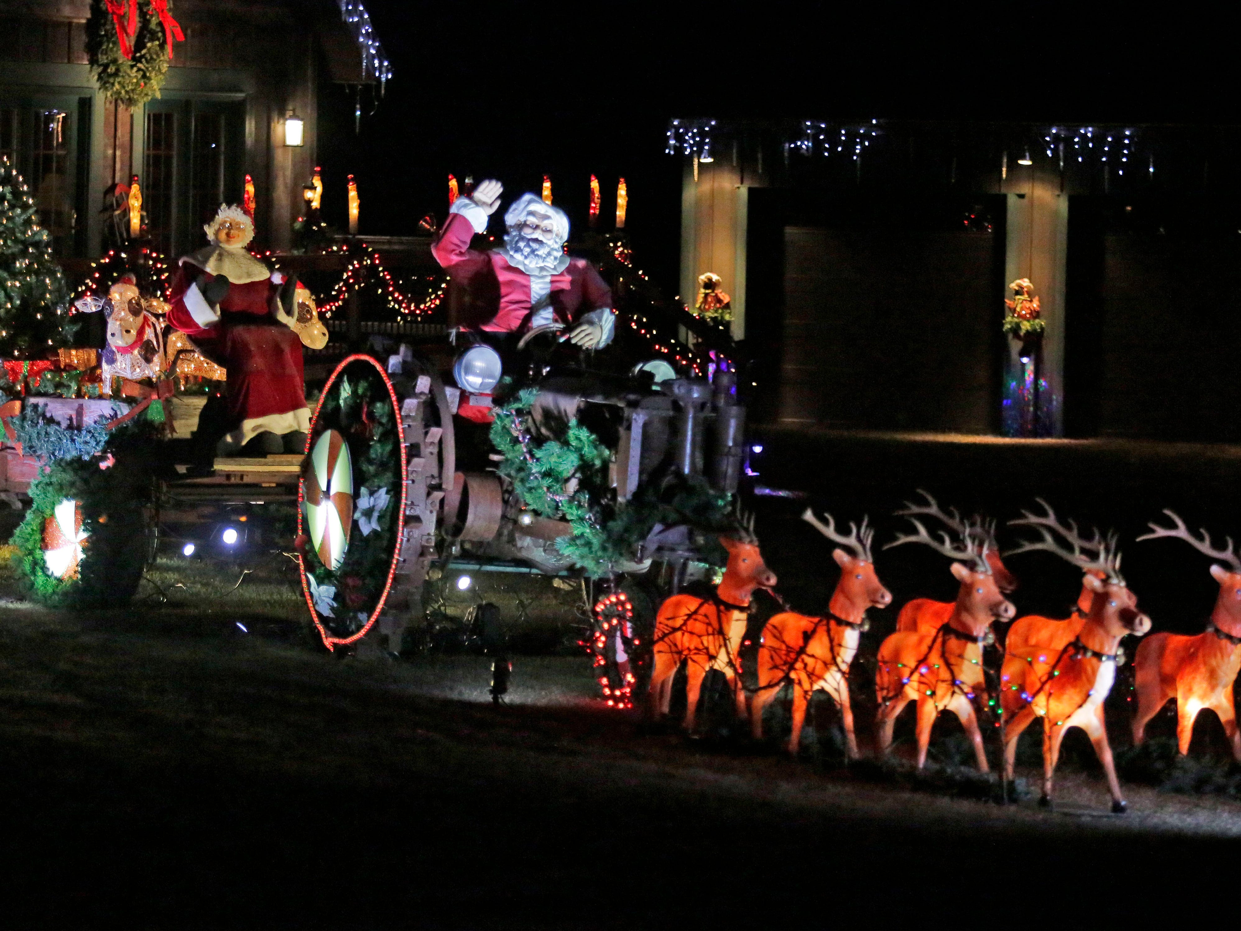 Santa commands his team of deer from a tractor along state Highway 57, Saturday, December 15, 2108, in Waldo, Wis.