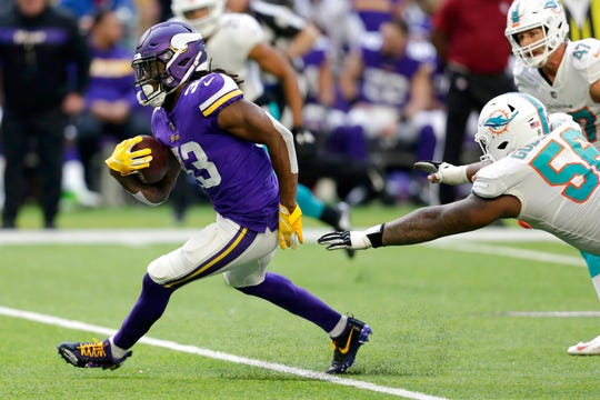 Minnesota Vikings running back Dalvin Cook (33) runs from Miami Dolphins outside linebacker Jerome Baker during the first half of an NFL football game, Sunday, Dec. 16, in Minneapolis.