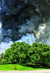 A firefighter runs toward his truck as the plume of black smoke from a fire at the Verso Paper Co. rises behind him May 28, 2012, in Sartell.