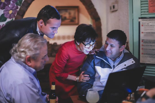 """District 8 city Rep. Cecilia """"Cissy"""" Lizarraga, Eddie Holguin and Chris Canales check the status of early voting results Saturday, Dec. 15, 2018, at G&R Restaurant."""